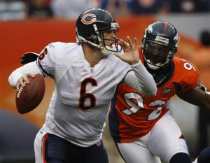 Chicago Bears quarterback Jay Cutler (6) scrambles out of the pocket to avoid the rush of Denver Broncos' Elvis Dumervil (92) during the first quarter of an NFL preseason football game in Denver on Sunday, Aug. 30, 2009. (AP Photo/Ed Andrieski )