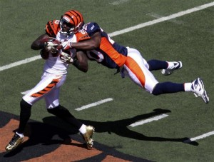Cincinnati Bengals receiver Chad Ochocinco (85) is tackled by Denver Broncos safety Brian Dawkins (20) in the first half of an NFL football game, Sunday, Sept. 13, 2009, in Cincinnati. (AP Photo/Tom Uhlman)