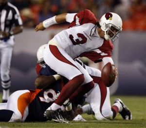 Arizona Cardinals quarterback Tyler Palko, front, is dragged down for a loss by Denver Broncos defensive lineman Tim Crowder in the fourth quarter of the Broncos' 19-0 victory in a preseason NFL football game in Denver on Thursday, Sept. 3, 2009. (AP Photo/David Zalubowski)