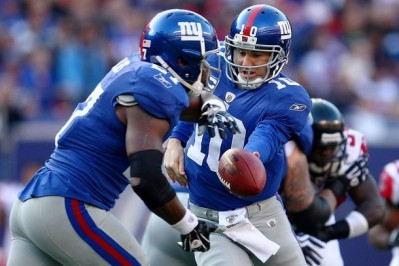 Eli Manning #10 of the the New York Giants hands off to team mate Brandon Jacobs #27 against the Atlanta Falcons on November 22, 2009 at Giants Stadium in East Rutherford, New Jersey.  (Chris McGrath/Getty Images)