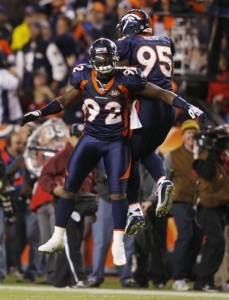 Denver Broncos defensive end Elvis Dumervil (92) and defensive tackle Darrell Reid (95) react after Dumervil sacked New York Giants quarterback Eli Manning during the fourth quarter of an NFL football game in Denver, Thursday, Nov. 26, 2009. Denver won 26-6. (AP Photo/ David Zalubowski)