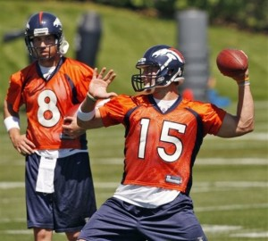 Tim Tebow sets up to pass as Kyle Orton watches during mini camp at the Broncos facility in Englewood. (AP Photo/Ed Andrieski)