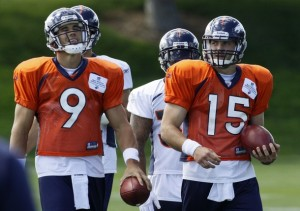 Denver Broncos quarterbacks (L-R) Brady Quinn and Tim Tebow walk down the field during practice in Englewood, Colorado July 30, 2010. Rookies worked out for three days before the veteran players report on August 1st. (REUTERS/Rick Wilking)