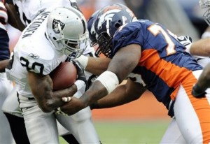 Oakland Raiders running back Darren McFadden (20) is tackled after a first down run by Denver Broncos defensive tackle Marcus Thomas (79) during the first half of an NFL football game, Sunday, Oct. 24, 2010, in Denver.  (AP Photo/ Jack Dempsey )