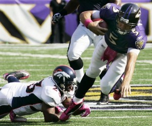 Baltimore Ravens quarterback Joe Flacco (5) rushes out of the pocket for a first down before being tripped up by Denver Broncos safety Renaldo Hill (L) during the third quarter of their NFL football game in Baltimore, Maryland October 10, 2010. (REUTERS/Joe Giza)