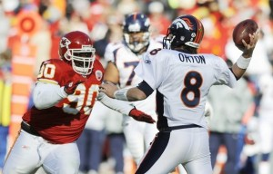 Denver Broncos quarterback Kyle Orton (8) passes just before Kansas City Chiefs defensive tackle Shaun Smith (L) reaches him in the first half of their NFL football game in Kansas City, Missouri December 5, 2010. (REUTERS/Dave Kaup)