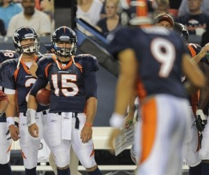 Denver Broncos quarterback Tim Tebow (15) and Denver Broncos quarterback Adam Weber (2) watch as quarterback Brady Quinn leads the offense in the second quarter of a preseason NFL football game, Saturday, Aug. 20, 2011, in Denver.  (AP Photo/Jack Dempsey)
