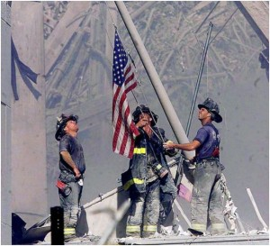 Firefighters raise the American flag following the tragedy of 9/11